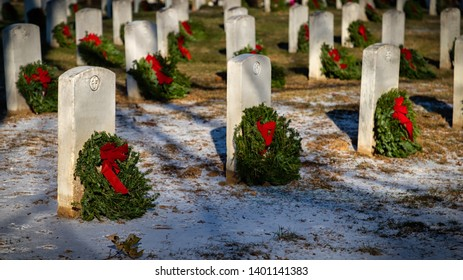 Arlington, Virginia / United States – December 16, 2017:  Holiday wreaths placed on gravestones at Arlington National Cemetery.