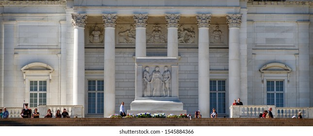 Arlington, Virginia / United States – October 3, 2017:  Spectators stand behind the Tomb of the Unknown Soldier protected by a member of The Old Guard at Arlington National Cemetery.