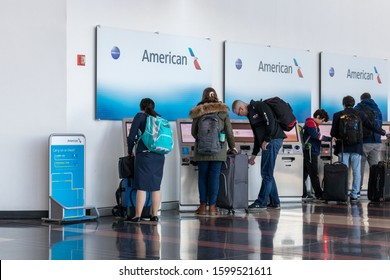 ARLINGTON, VIRGINIA, USA: December 12, 2019 - People are seen using self-serve check-in kiosks for American Airlines inside Ronald Reagan Washington National Airport.