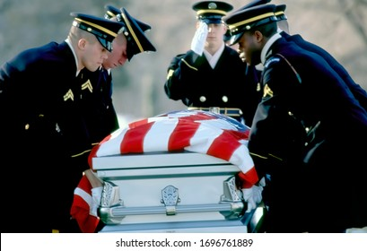Arlington, Virginia, USA, December 28,1989 The Burial detail lowers the flag draped casket of Specialist Alejandro L. Manrique 30, at his gravesite. Manrique was buried with military honors,