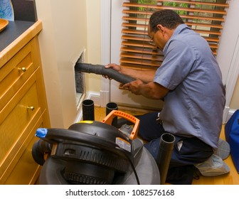 ARLINGTON, VIRGINIA, USA - JULY 2, 2009: Worker with vacuum during duct cleaning in home.