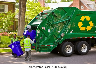 ARLINGTON, VIRGINIA, USA - JUNE 23, 2009: Workers empty recycling bins into truck in residential neighborhood.