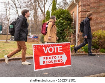 ARLINGTON, VIRGINIA, USA - MARCH 3, 2020: Democratic primary election voters arrive at Lyon Village polling place, passing Photo ID Required sign.