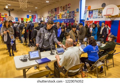 ARLINGTON, VIRGINIA, USA - NOVEMBER 6, 2018: Election officials check voters identification during midterm election voting, at Key School.