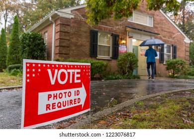 ARLINGTON, VIRGINIA, USA - NOVEMBER 6, 2018: Midterm voters arrive at polls during rain storm, Lyon Village Community Center.