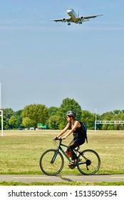 Arlington, Virginia / USA - September 11, 2019:  A woman rides her bicycle at Gravelly Point Park as a Jet Blue regional flight prepares to land at Ronald Reagan Washington National Airport.