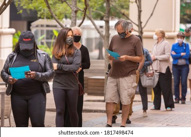 ARLINGTON, VIRGINIA, USA - SEPTEMBER 18, 2020: People line up and look at sample ballots during first day of early voting, 2020 presidential election.