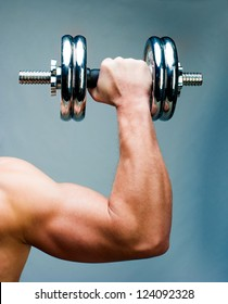 Arm attractive athletic man with dumbbells
