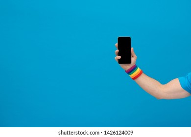 Arm or biceps of a man wearing a bracelet with the gay pride flag holding a smart phone on a blue isolated background for copy space with space to write on the left side