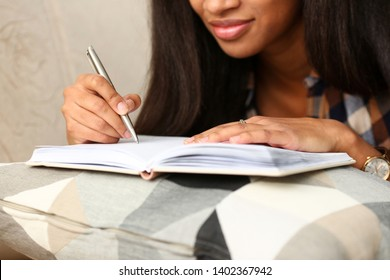 Arm of black woman write story in notebook preparing for college