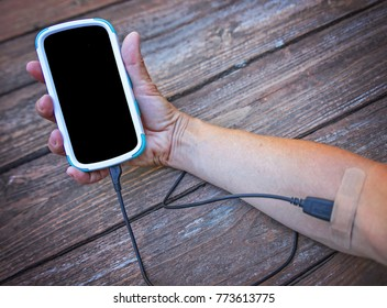 an arm with a cell phone hooked intravenously with the charger cord and a band aid covering the end tip - social media addiction concept