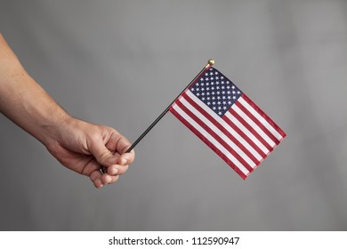 An arm is extended and holding an American Flag.