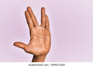 Arm and hand of black middle age woman over pink isolated background greeting doing vulcan salute, showing hand palm and fingers, freak culture