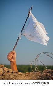 Arm holding stick with a white flag. Soldier in trench with barbed wire surrendering in war battle.