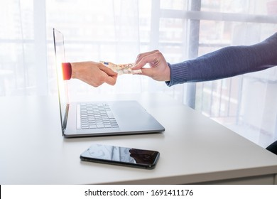 An arm leaves the computer to deliver or collect money from an internet user