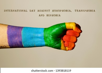 the arm of a man, painted as the rainbow flag, and the text international day against homophobia, transphobia and biphobia, against an off-white background