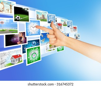 Arm pointing at holographic pictures on abstract background