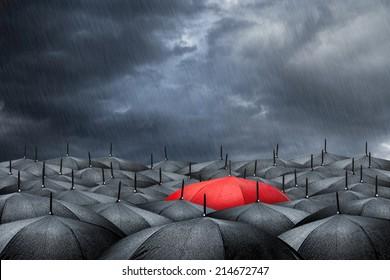 arm with red umbrella in mass of black umbrellas