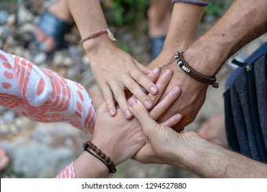 Arm stacked together one by one in unity and teamwork. Many hands getting together in the center of a circle. Close up outdoor shot. Many hands connecting in nature.