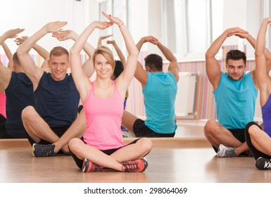 Arm stretching after workout inside fitness class