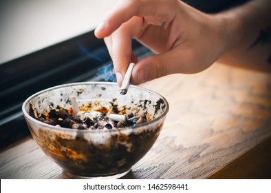 Arm with a tattoo holding a smoldering cigarette and shaking off the ashes in a glass vile dirty ashtray filled with butts, which stands on a wooden window sill.