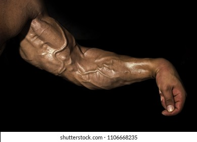 arm wrestler. Arm with muscles, biceps, triceps and veins on black background. Power, strength concept. Sport, fitness, bodybuilding.