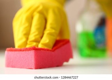 Arm in yellow latex protective glove wiping off dust and dirt from white table surface closeup. Doing up household maid manual worker liquid foam business concept