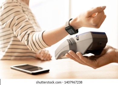 Arm of young modern woman with smartwatch on wrist keeping it over electronic machine while paying for goods or service