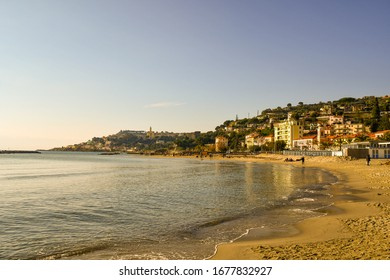 Arma di Taggia, Imperia / Italy - January 02 2020: Scenic view of the beach with the Sanctuary of the Sacred Heart of Bussana and Capo dell'Arma cape in the background in a sunny winter day