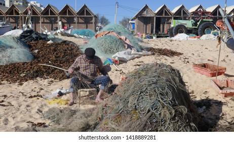 Armacao de Pera, Algarve, Portugal - 03/13/2019 :  Fishermen at work after fishing at Fishermen's Beach in  Armacao de Pera