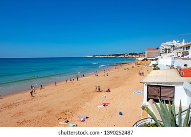 Armacao de Pera, Portugal - April 21, 2019: People enjoying at the beach in Armacao de Pera in the Algarve Portugal