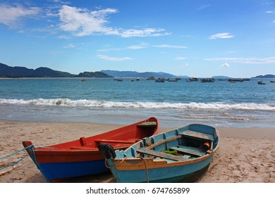 ARMACAO, FLORIANOPOLIS, SANTA CATARINA, BRAZIL. Panoramic view of the sea, early in the morning from the beach. In the foreground you can see two colorful boats on the beach.