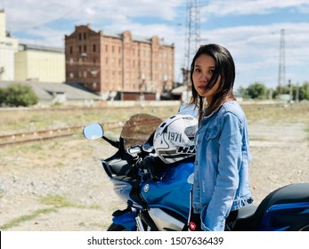 Armavir / Russia - September 17 2019: A girl of Asian appearance next to a motorcycle on the background of an abandoned building.