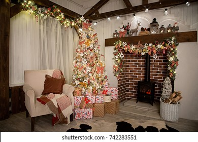 An armchair near a decorated Christmas tree and a fireplace