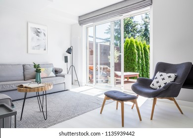 Armchair with patterned pillow and stool in living room interior with grey sofa and posters. Real photo
