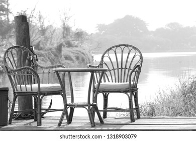 Armchair put on wooden balcony by the river in the midst of nature in black and white.