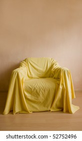armchair with yellow bed sheet