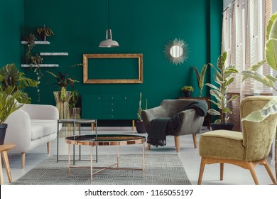 Armchairs and sofa next to copper table in green apartment interior with mockup of frame. Real photo