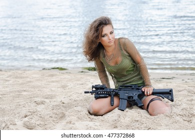 Armed beautiful young woman in camouflage with rifle on the beach. Military, army and war concept