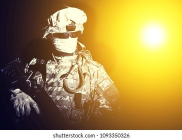 Armed infantry with hidden face standing in blinding light of projector or searchlight during combat, counter terrorist night raid, protected perimeter control, state border patrolling and protecting