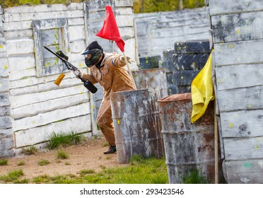 Armed man setting up victory flag in paintball mission
