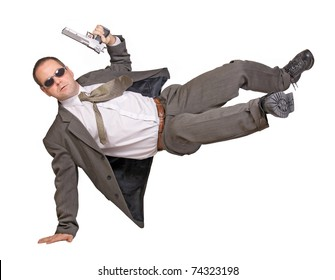 Armed man in a suit jumping. Police agent in action. A security guard in a suit jumps with a gun. Businessman with a gun. Action hero with a gun jumps isolated on a white background.