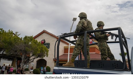 Armed Mexican marines on the streets of La Paz Mexico riding in the back of a pick up truck during spring break in March of 2019. Patrols of local militia are common in this city.
