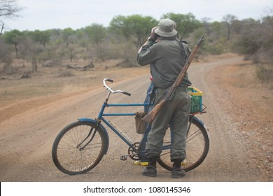 Armed Park Ranger standing near his bike looking through a binoculair for game or danger on a dirt road