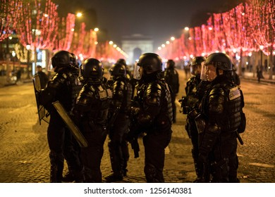 "Armed police force in front of Arc De Triomphe in the night during the ""Yellow Vests"" antigovernment protest in the French capital. Paris, France - December 8, 2018"