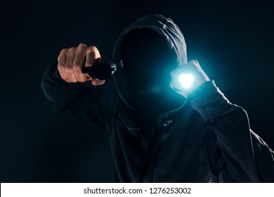 Armed robbery, criminal with hoodie holding gun and torchlight and attacking in dark, low key selective focus