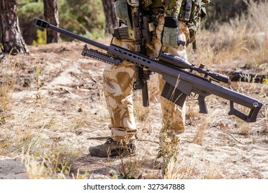 Armed soldier holding large caliber sniper rifle during military training in forest