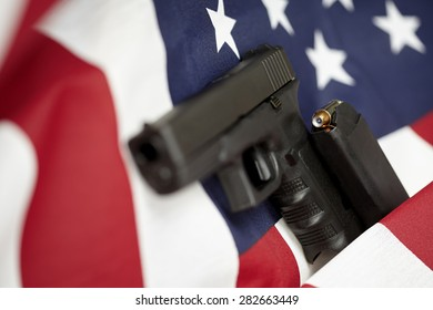 Armed United States of America gun and USA flag selective focus closeup