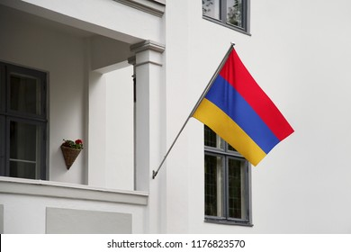 Armenia flag. Armenian flag hanging on a pole in front of the house. National flag waving on a home displaying on a pole on a front door of a building. Flag raised at a full staff.