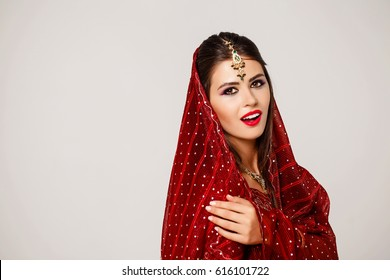 Armenian beauty. Close up portrait of beautiful woman in red sari on a gray background